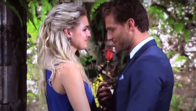 Juan Pablo in a suit gives Nikki Ferrell in a blue dress a rose