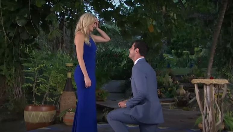 Lauren Bushnell in a blue dress standing in front of Ben Higgins while he gets down on one knee to propose