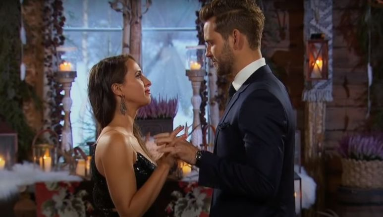Nick Viall in a suit proposing to Vanessa Grimaldi wearing a black dress