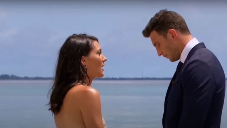 Becca Kufrin standing with Blake Horstmann with the sky in the background