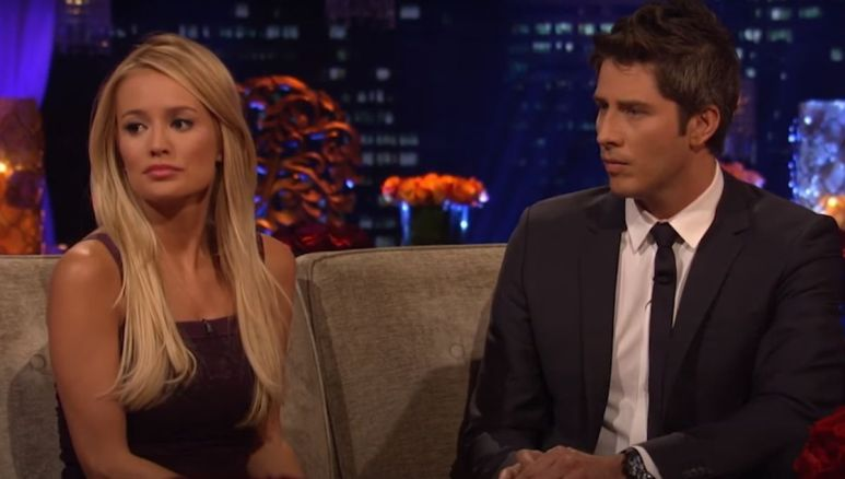 Emily Maynard in a dress sitting next to Arie Luyendyk Jr. on a tan couch