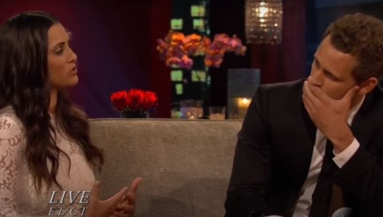 Andi Dorfman in a white dress sitting next to Nick Viall on a couch