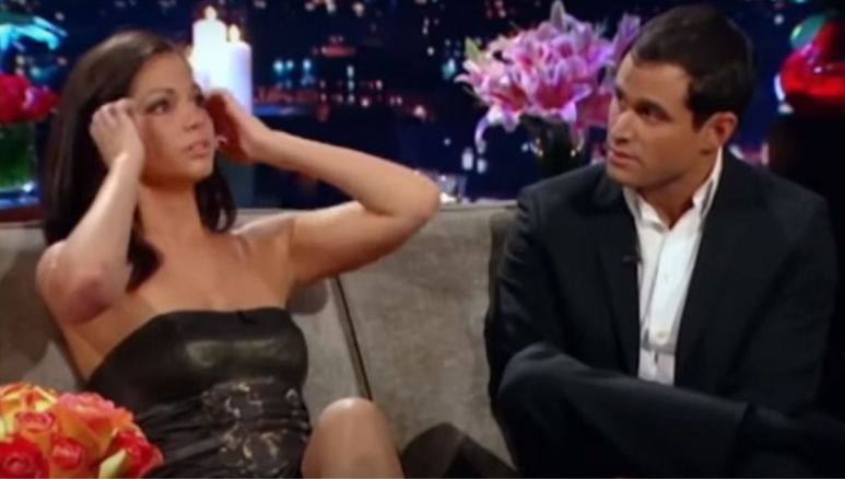 Melissa Rycroft in a black dress with her hands to her head sitting next to Jason Mesnick on a couch