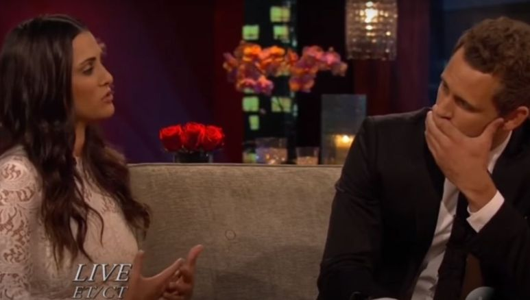 Andi Dorfman sits on a couch next to Nick Viall as they converse