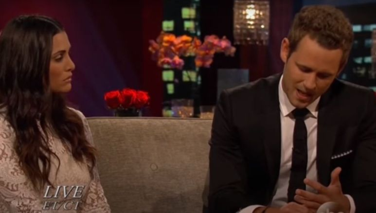 Andi Dorfman sits in a white dress on The Bachelor couch next to Nick Viall in a suit