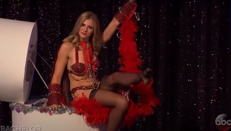 Olivia Caridi in a red showgirl costume on stage