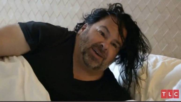 Big Ed poses in bed on 90 Day Fiance.