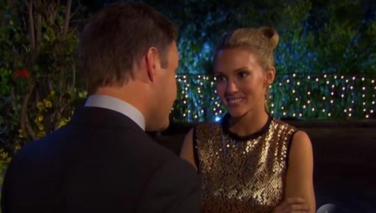 Chris Harrison talks to Rozlyn Papa as she smiles in a gold dress at night