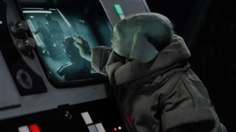 Grogu reaches out to a screen showing Luke Skywalker