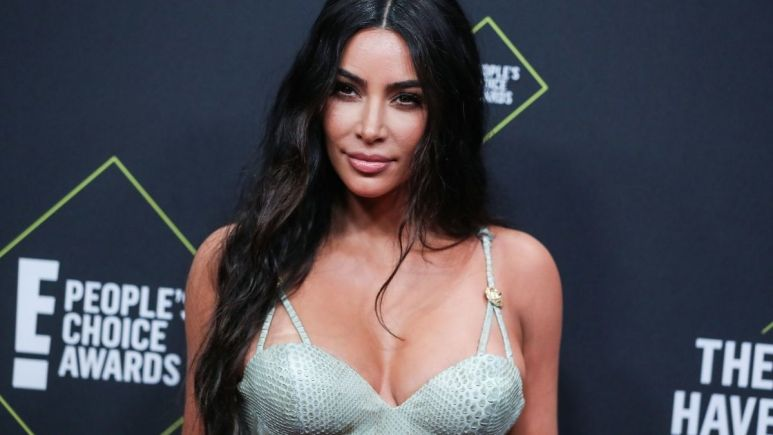 Kim Kardashian in a light green dress, posing at the People's Choice Awards.