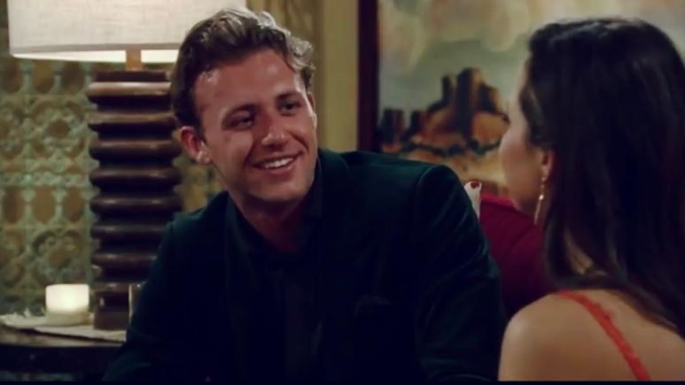 Christian Smith wears a suit and smiles while sitting on the couch with Katie