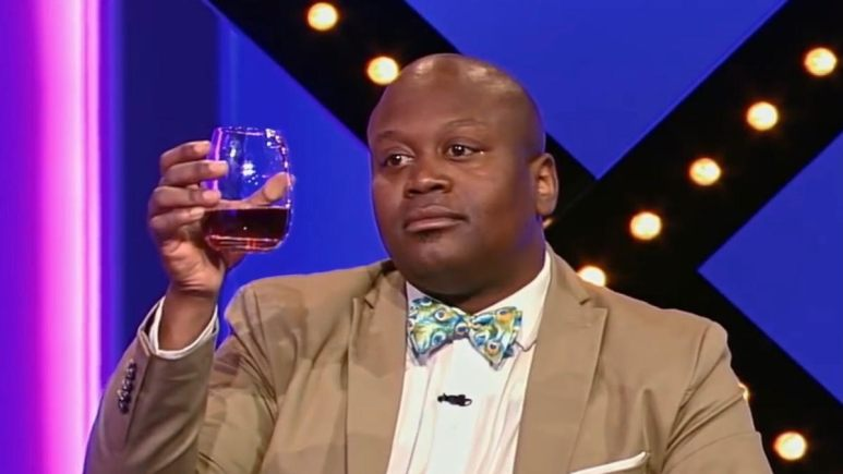 Tituss Burgess holds up a glass of wine while wearing a tan suit and colorful bowtie