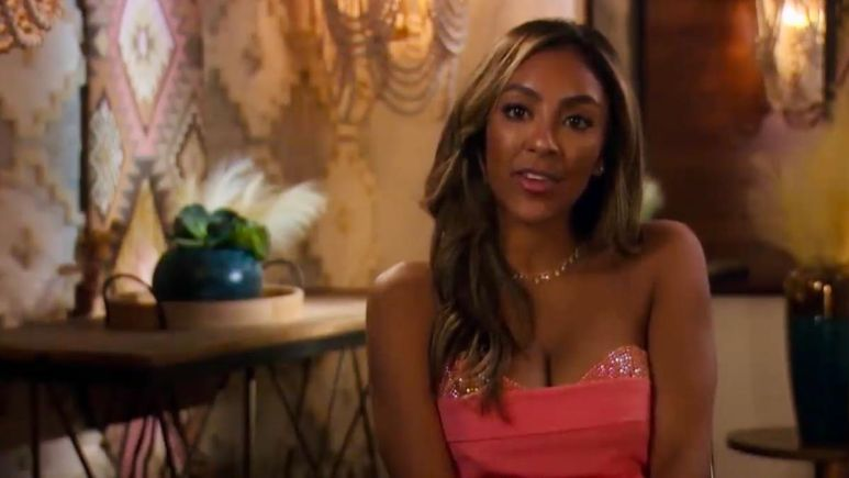 Tayshia Adams wears a colorful dress while looking at the camera