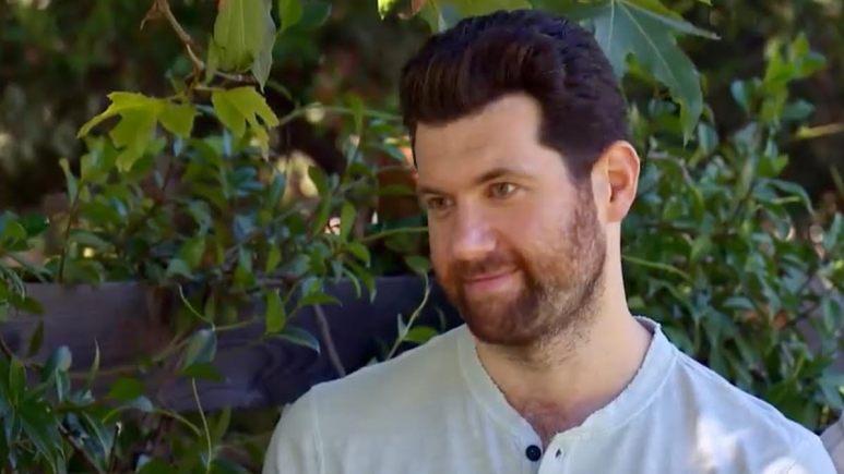 Billy Eichner smirks in front of greenery