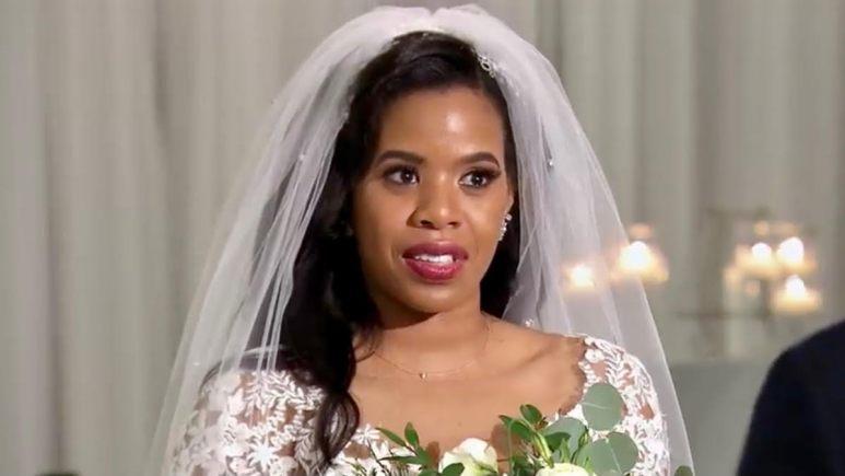 Michaela wears a wedding dress and veil at the altar