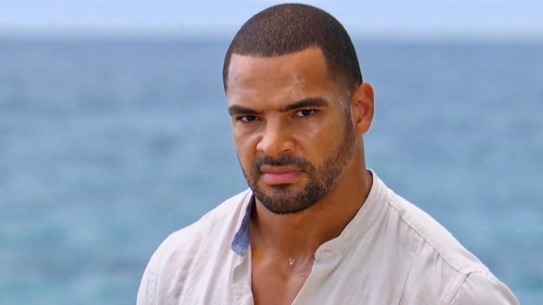 Clay Harbor stares at the camera by the ocean