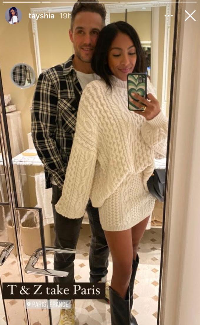 Tayshia Adams and Zac Clark pose in a mirror