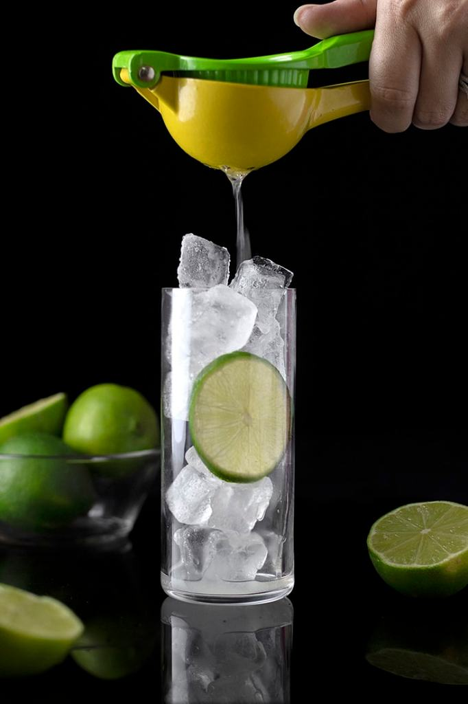 squeezing lime juice over ice in a tall glass