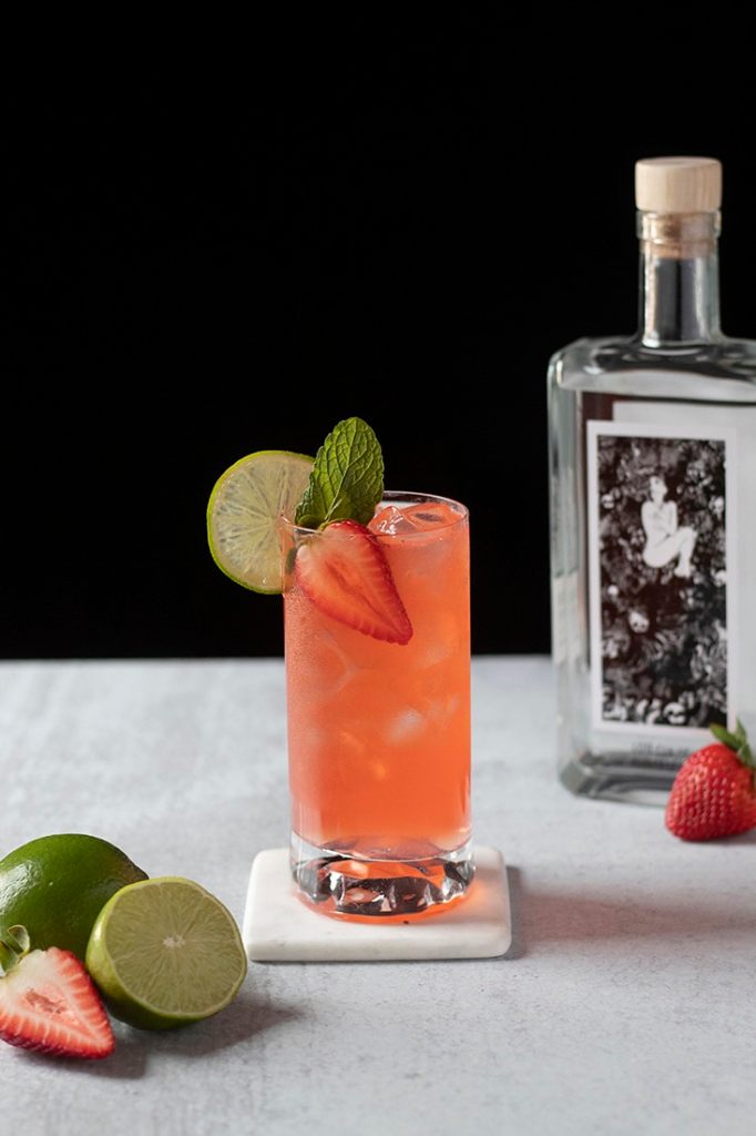 an orange cocktail in a highball glass garnished with lime and strawberry