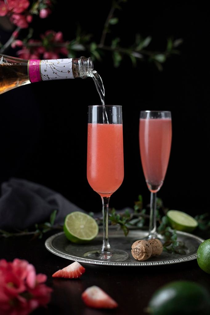 pouring pink sparkling wine into champagne flutes