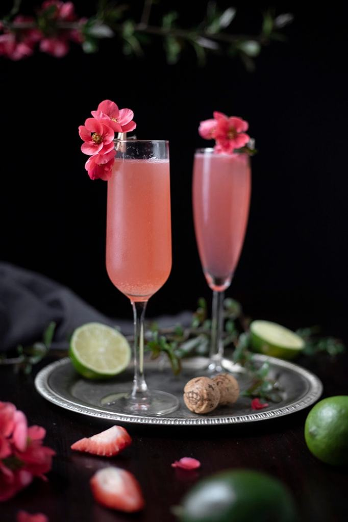 close up of two pink cocktails in champagne flutes garnished with pink quince blossoms