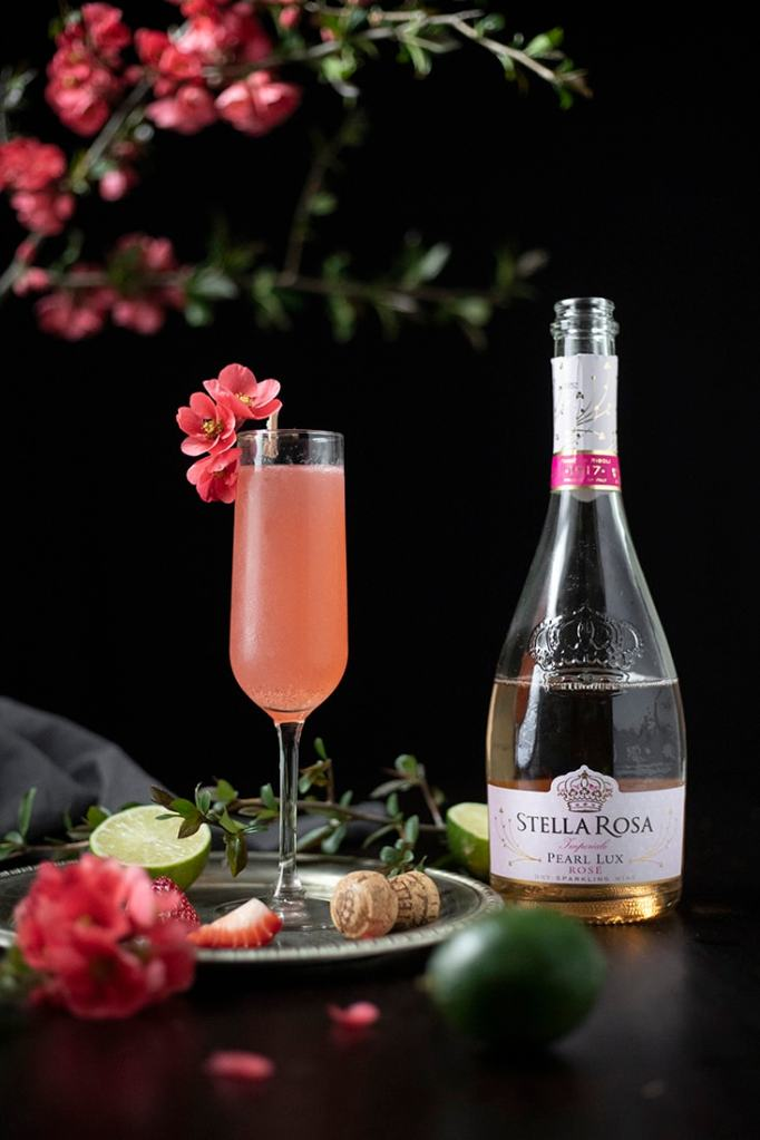 close up of pink cocktail in a champagne flute next to a bottle of sparkling rose wine