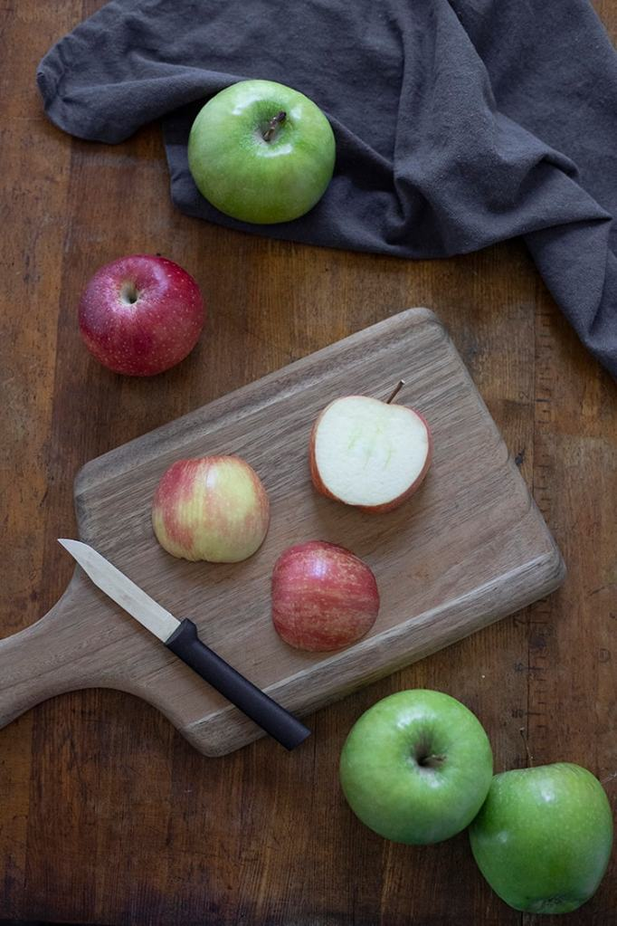 a cutting board with apples demonstrating two ways to position the halves of the apple before cutting apple fan slices