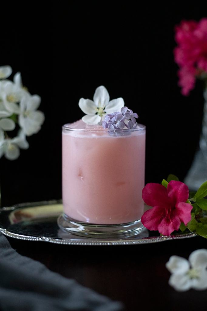 pale pink drink on a silver tray with the focus on a purple lilac flower garnish
