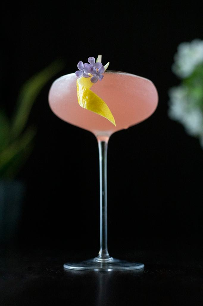pink cocktail on a black background with a lemon twist and flower