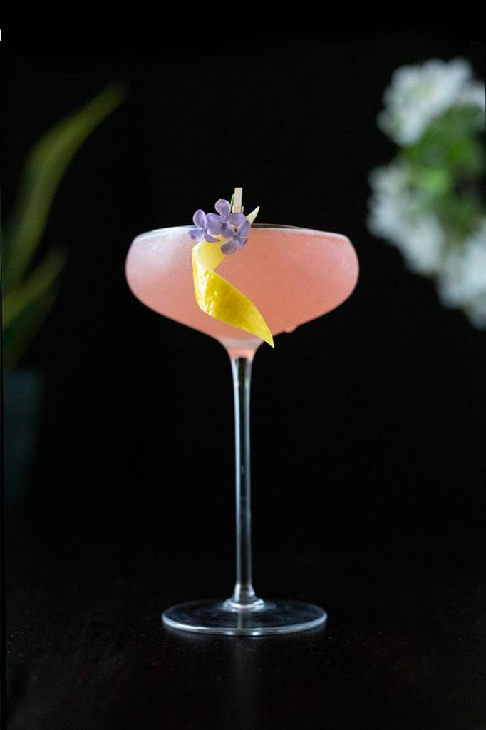 a rosy pink cocktail on a black background with a lemon twist garnish and three small lilac blooms