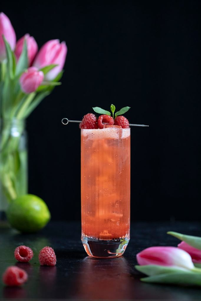 tall reddish orange clear bubbly drink garnished with raspberries and mint