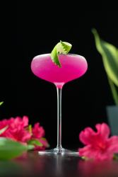 neon pink cocktail in a tall coupe glass with a lime twist