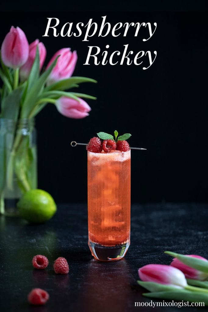 red drink in a highball glass on a black marble table with pink tulips