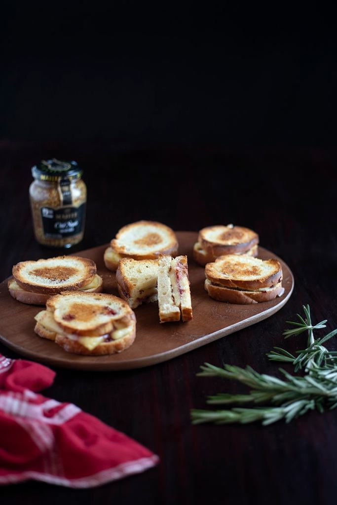 miniature grilled cheese sandwiches on cutting board