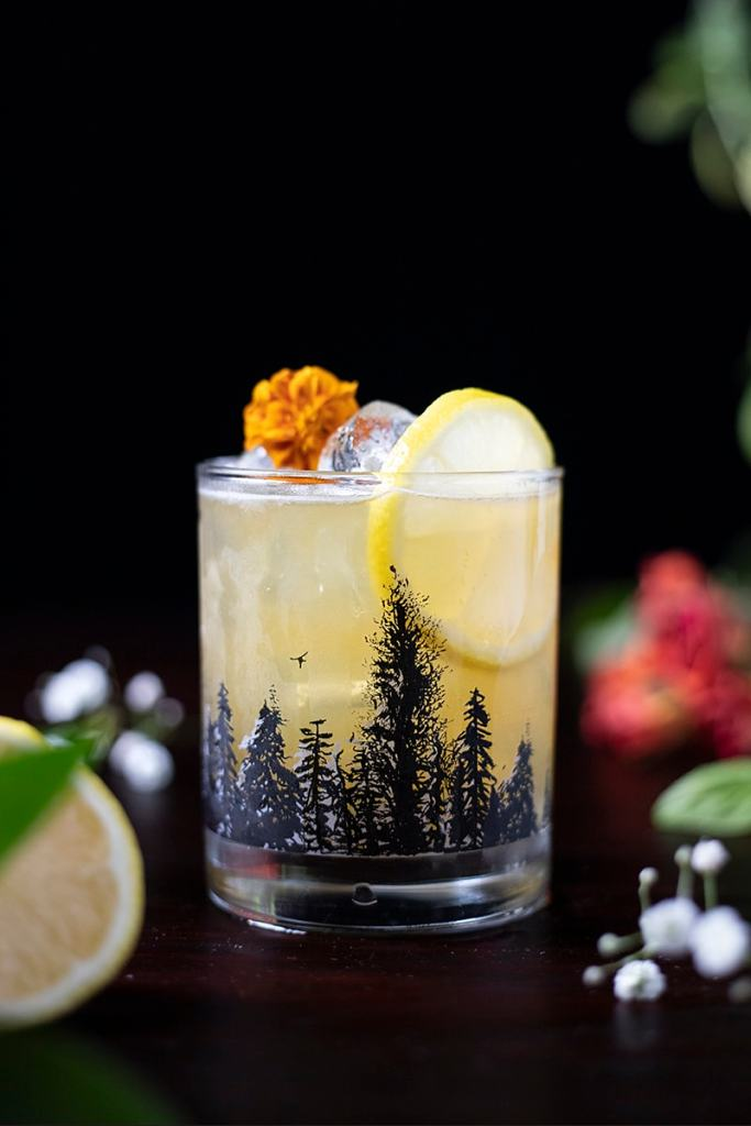 yellow cocktail in rocks glass with black silhouettes of pine trees etched onto glass