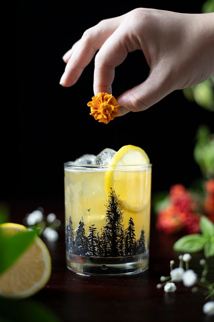 a hand adding an orange flower to a cocktail