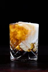 a rocks glass filled with swirling layers of white cream and brown liquors