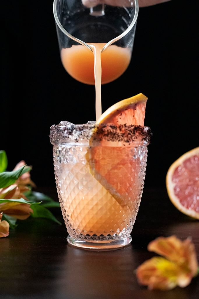 pouring grapefruit juice into a double rocks glass