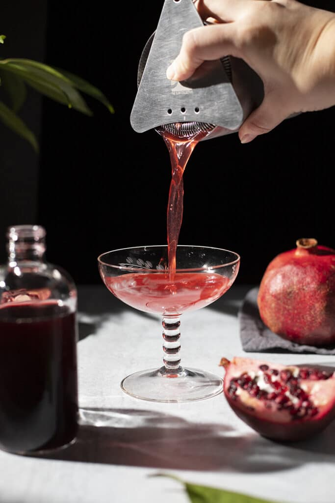 pouring a red cocktail from shaker to cocktail glass