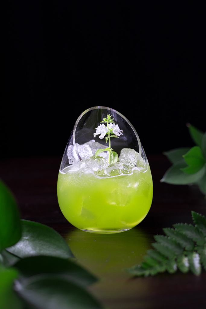 a green drink in a fancy stemless glass with a white flower.