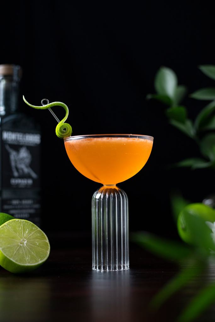 orange Naked and Famous cocktail in a coupe glass with a fancy lime peel garnish.