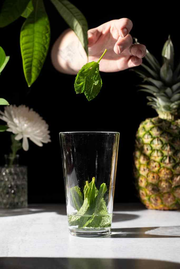 dropping mint leaves into a cocktail shaker