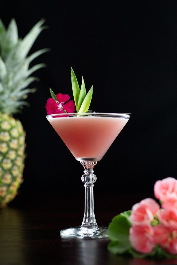 a pink cocktail with a pineapple and pink flowers.