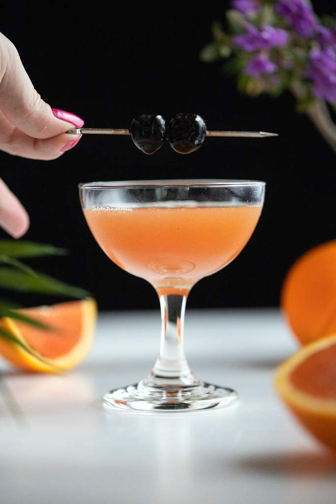 garnishing an orange cocktail with two cherries on a pick.
