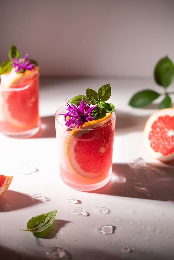 top down view of pink flower and basil leaf garnish.