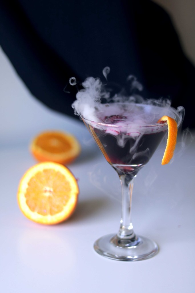 Spooky black magic Samhain cocktail. Step through the Veil Between Wordls with this dramatic dry ice martini recipe.