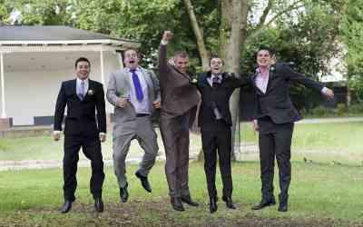 Bruidegom en vrienden springen op de bruiloft