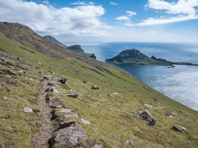 Wandelpad en beneden het grillig gevormde eiland Tindhólmur