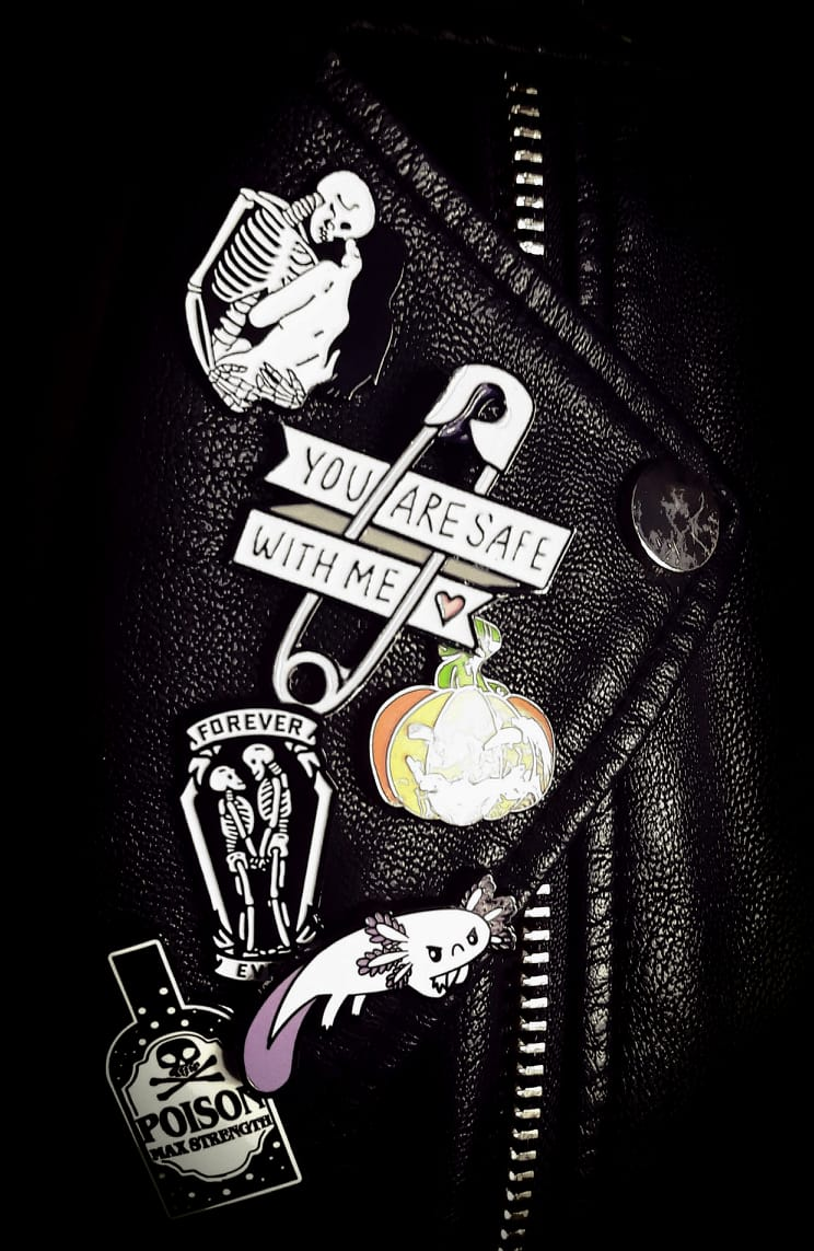 Several pins on a leather jacket lapel, focused on a safety pin with a banner reading'you are safe with me'