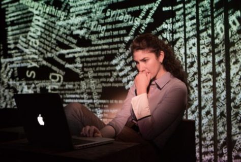 A woman staring at a laptop screen. A mess of internet comments projected on the surface behind her.